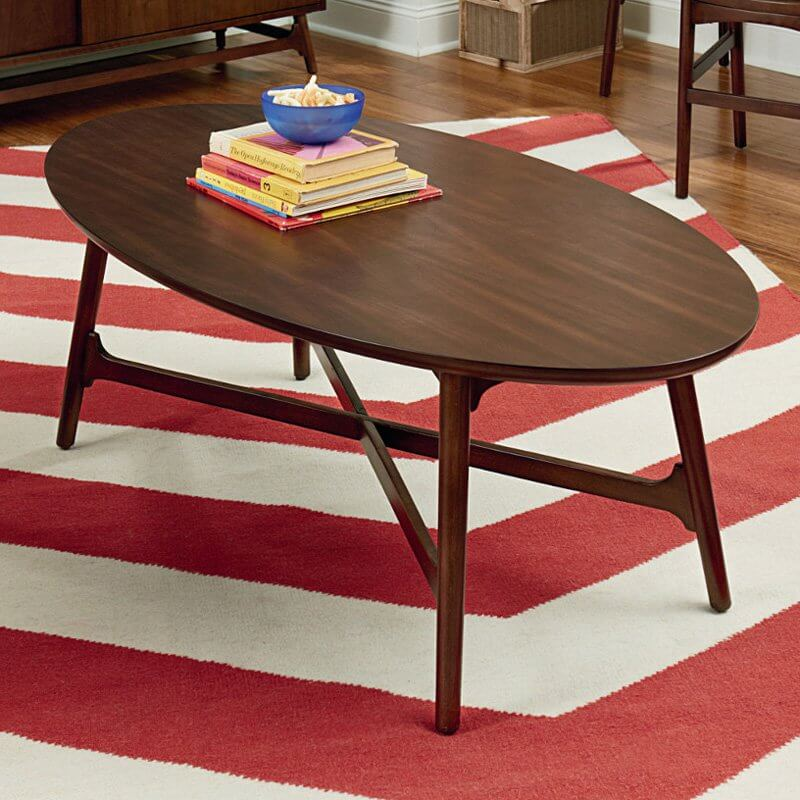 This large, classically shaped coffee table in rich dark brown wood features a sturdy cross-bar frame between the slim, elegant legs.