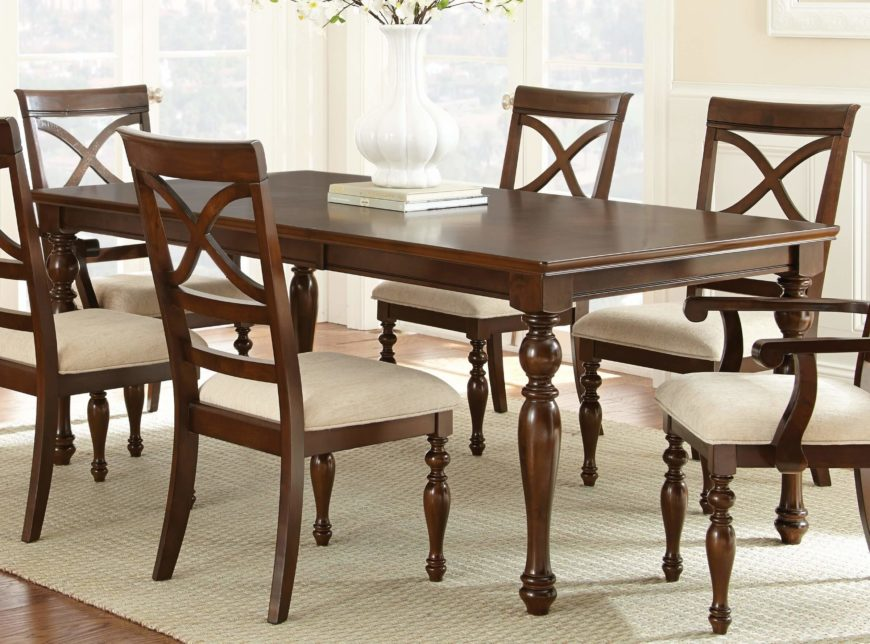This traditionally styled dining room table features ornate, carved legs with an arrow foot design beneath the expanse of rich, sleek hardwood surface.