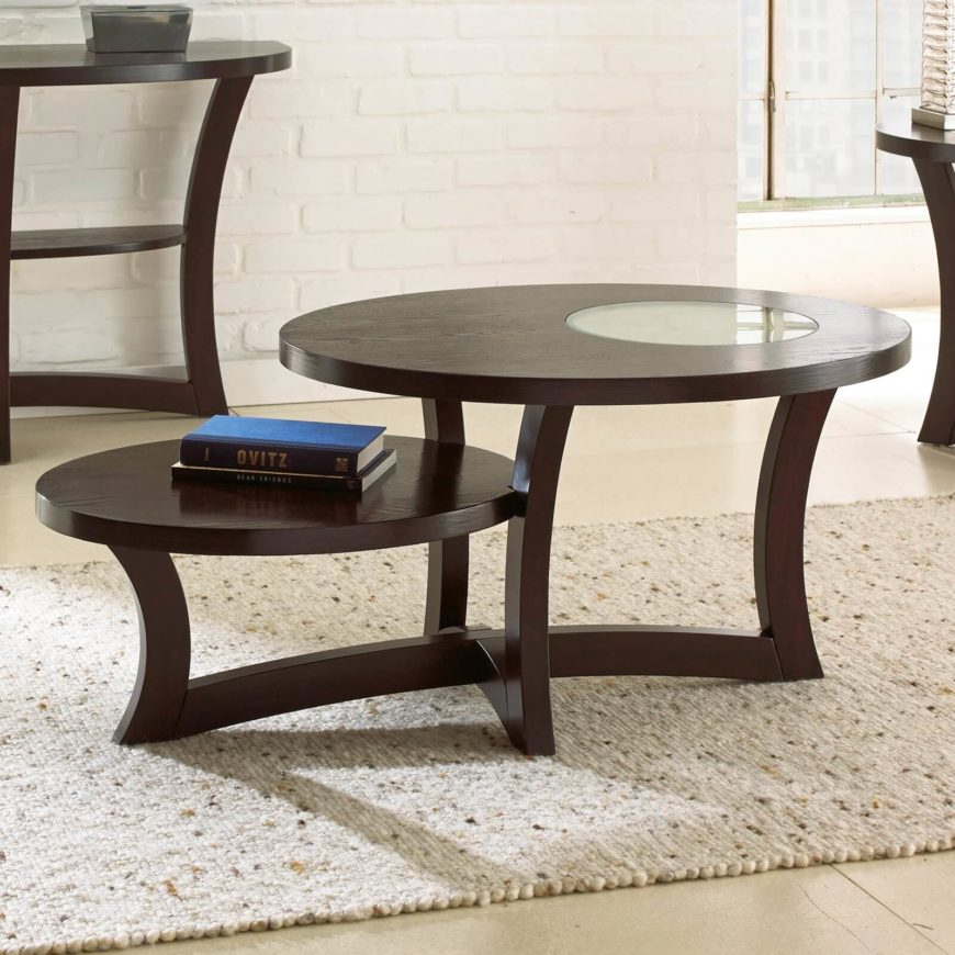 This contemporary coffee table features an interesting two-tiered design, with a smaller oval surface staggered next to the main surface. A unique smoked glass insert helps this table stand apart.