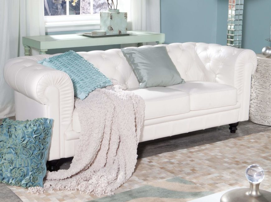 This stately sofa features a wide roll-arm design that continues into the thickly padded back. Button tufted vertical surfaces meet smooth seat cushions.