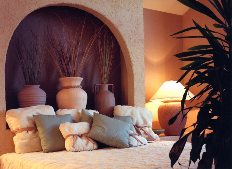 This delightful Santa Fe style arrangement features simple pillows in complementary neutrals. A slightly disheveled look makes this space soft and welcoming. A soft tie is wrapped around the cream colored pillows, while the light gray square accent pillows are loosely arranged.
