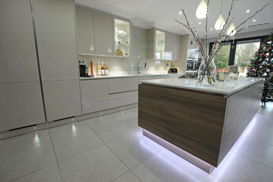 The island visually floats over the large format tile flooring, with a series of lighting strips. The dark wood grain adds contrast to a mostly white space.
