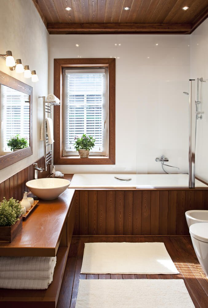 This slim, minimalist bathroom flaunts the natural hues of dark toned hardwood, with flooring, vanity, and soaking tub enclosure in the material. White walls and porcelain basins add contrast, along with matching towels and rugs.
