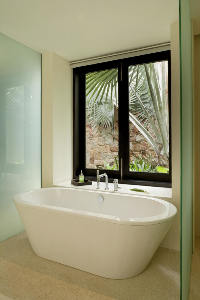 One of the home's bathrooms has a free-standing soaking tub that looks out over the palms. Frosted glass panels help keep the splashes to a minimum, and provide a small sense of privacy as well.