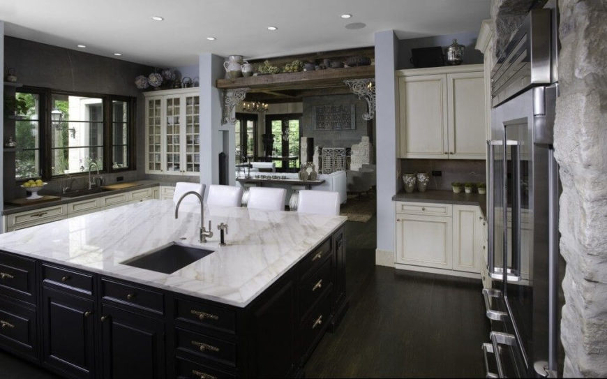 The eat-in kitchen island is black and white with a narrow sink slightly off-center. The kitchen's widest archway leads back into the living room.