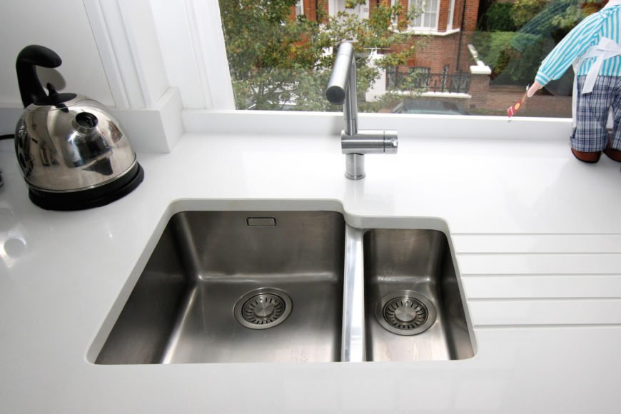 Unique sink design embeds the basin within the thick white countertop. Here we see the view enjoyed by this kitchen.