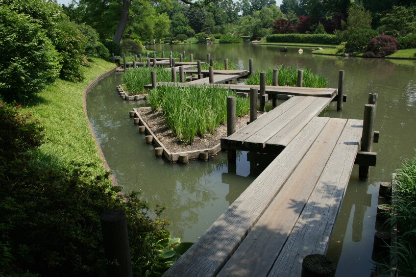 This zig-zagging garden bridge design carries visitors over a lengthy pond and across several small grassy island planting beds. The whole of the garden is covered in lush greenery.