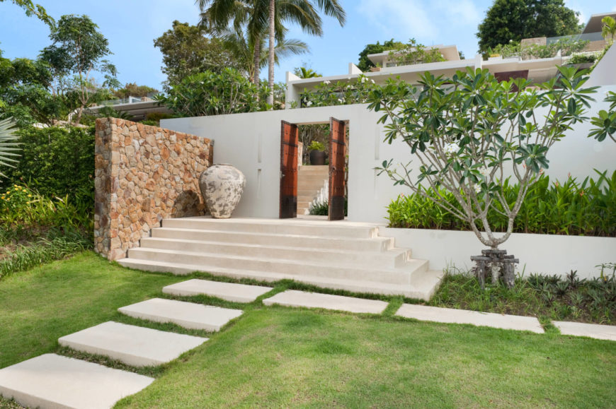 The rear of the home and entrance to the true backyard, via old-world style double doors and a set of steps leading down into the flagstone path. Above the wall we can see the various staircases and glass balustrades of the home's multiple levels, all landscaped beautifully.