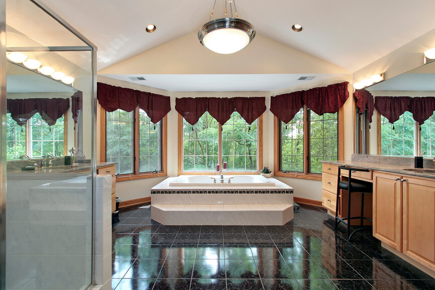 This grand, vaulted ceiling bathroom sports black tile flooring, a large expanse connecting a pair of full featured vanities and large soaking tub. An array of bay windows and rich natural hardwood offers expansive views and a natural touch.
