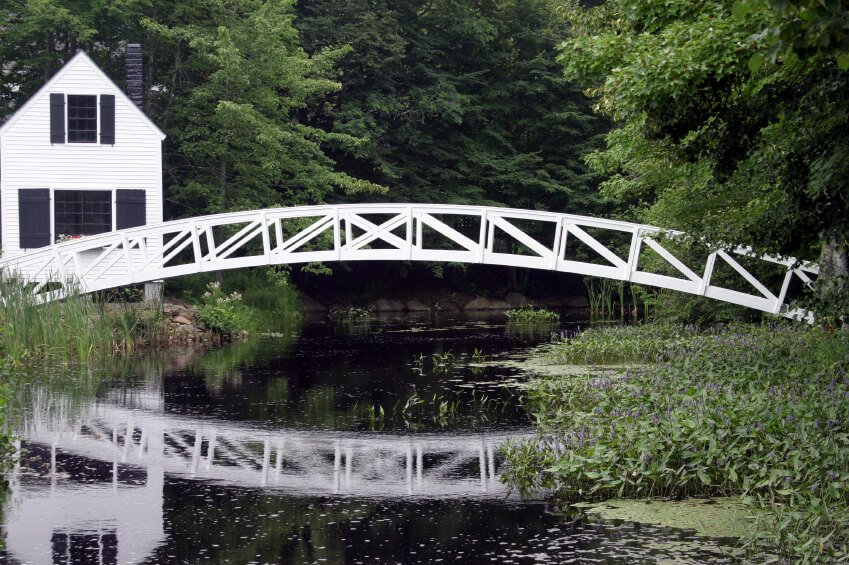 This incredible white footbridge bridges an enormous gap with no supports in the center. The style brings to mind a country cottage, which is complemented by the lovely shutters on the windows of the home behind the bridge.