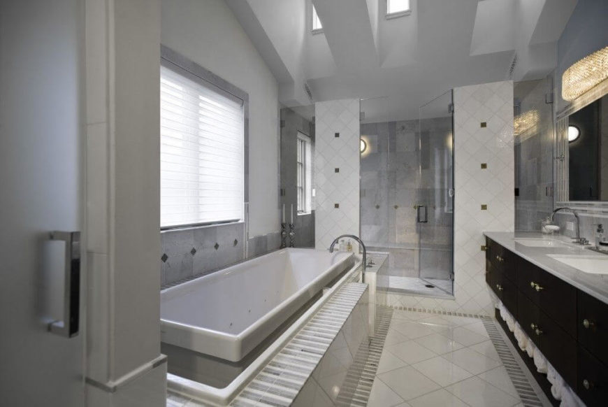 The primary bathroom returns to the more contemporary feel of the kitchen, in black, white, and gray. Open storage beneath the vanity is perfect for towels. The tile and glass shower enclosure has a long bench along the back.