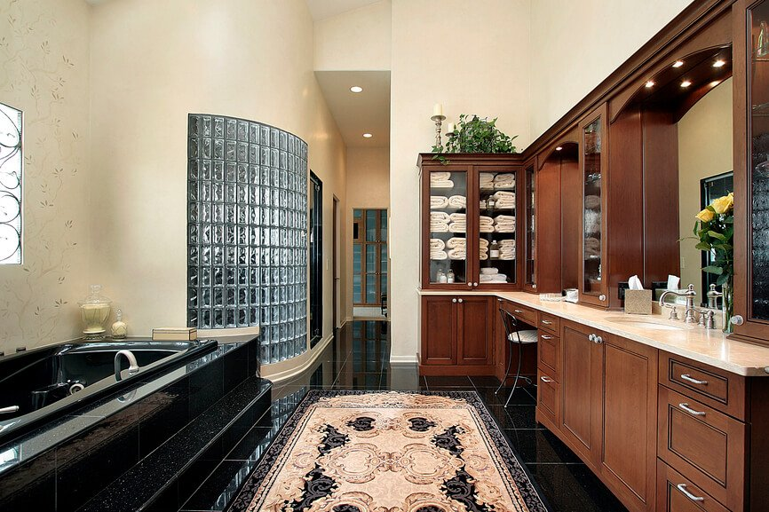 Here's another bathroom featuring jet black tile flooring, contrasting neatly with rich natural wood cabinetry and beige walls. A lengthy vanity at right features marble countertops, while the soaking tub and glass brick-enclosed shower stand on left.