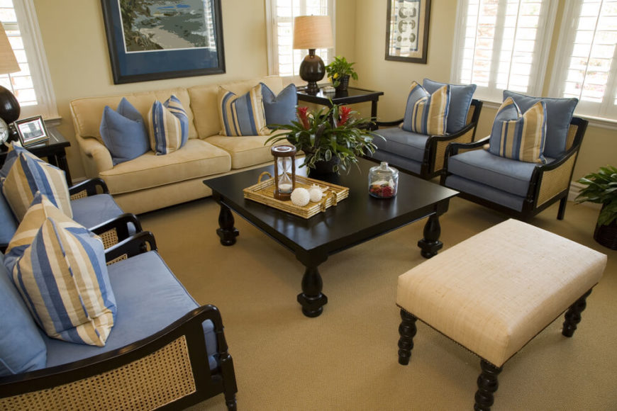 A small, nautical themed living room in light blue and beige with two end tables on either side of the loveseat. Each table is host to a lamp and several small accent pieces. The dark wood matches on every piece of furniture.