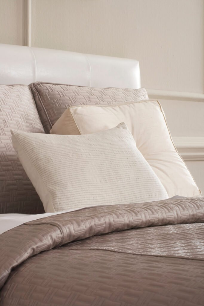 Plush square pillows in complementary neutrals host a lone oblong pillow with subtle striping.