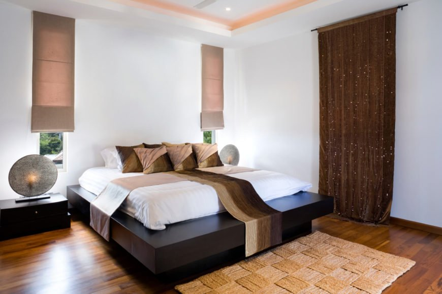 Inside, one of the bedrooms has a large dark wood platform bed and narrow windows. A natural fiber area rug covers the polished bamboo flooring.
