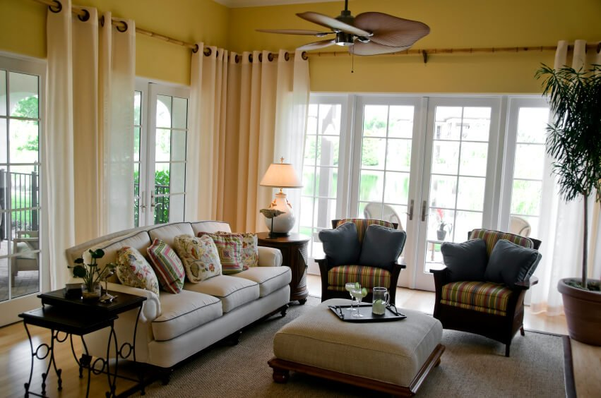 This casual living room and sunroom has bamboo curtain rods that extend around the perimeter of the room. Sheer curtains on grommets can easily be shifted around the room.