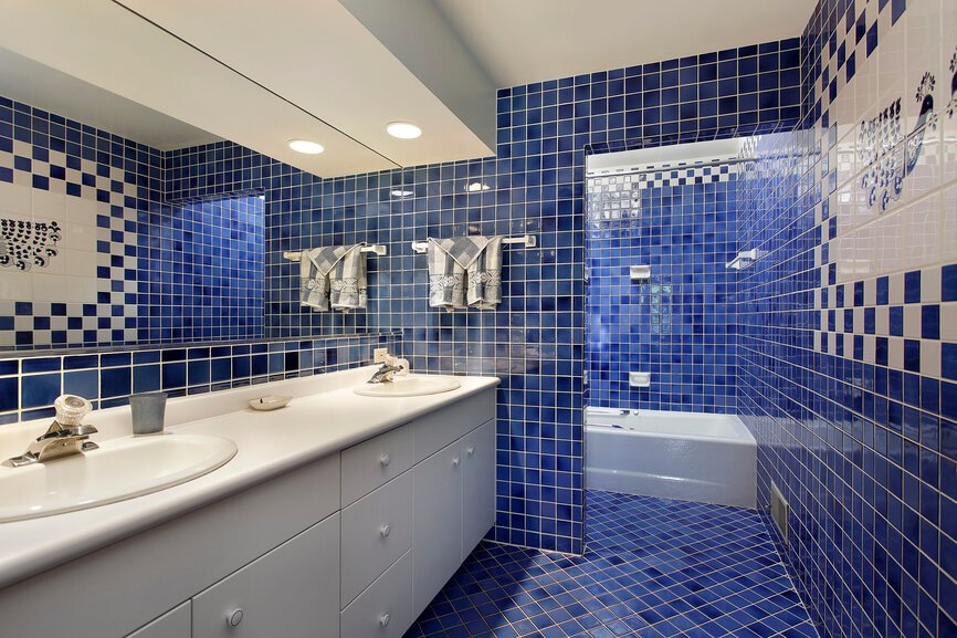 Here's a unique bathroom, even within this gallery. Bold blue tile stretches across the floor and up the walls toward a white ceiling, wrapping a large white dual vanity and soaking tub.