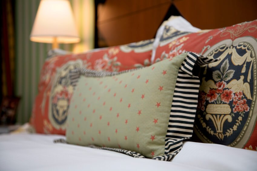 This bedroom space features richly patterned and vibrant throw pillows.