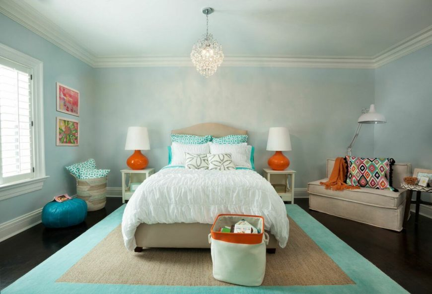 A chic, contemporary bedroom with soft ruffled bedding and a color palette of light blue, turquoise, and orange. A wide settee is in the right corner, with a soft throw blanket and a bold pillow. A delicate crystal chandelier hangs above the center of the bed. An adjustable floor lamp provides perfect reading light above the settee.