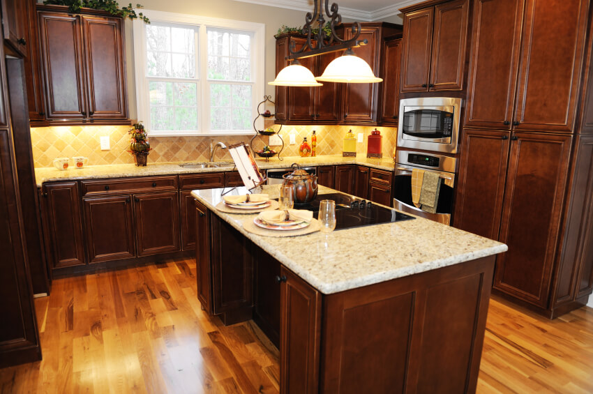 This sharp kitchen utilizes the light wood floor, bright backsplash, and white countertops to coordinate and off-set the dark cabinets. The large island houses cabinetry, a range, and space for two diners.