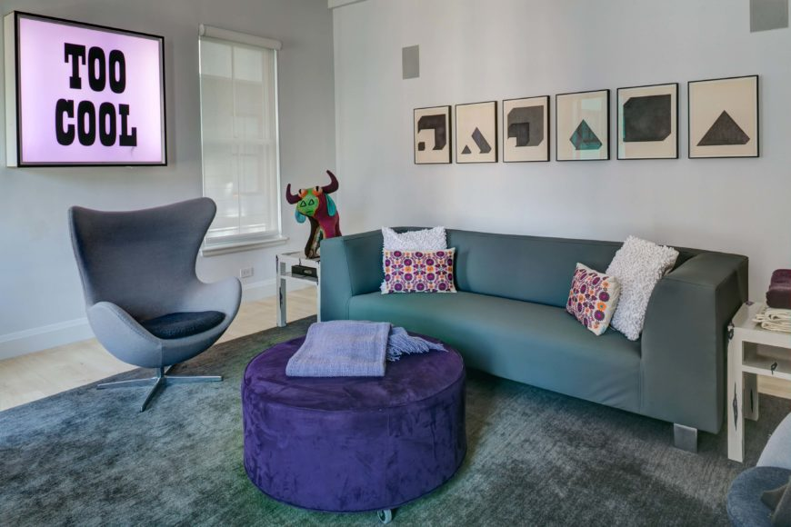 A casual and modern living room in blues and purple with a single small end table in a distressed white paint. A small shelf below the table top acts as open storage for a book or several magazines. The velour purple ottoman is on wheels and serves as both a footrest and as a coffee table.