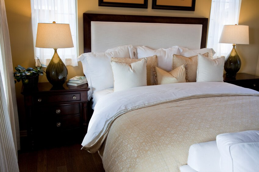 Gold, white, and ivory tones are offset by deep, rich hardwood furniture. The padded headboard supports a host of accent pillows that complement the rest of the room beautifully.