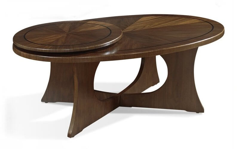 This richly detailed coffee table features an intricate wood grain pattern on both the oval surface and a unique circular platform that can be rotated outward for expanded surface area. Thick legs create a solid framework.