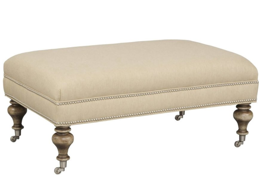 A large ottoman in cream with curvaceous legs on coasters and nailhead trim. Simple elegance that is easy to move around the room!