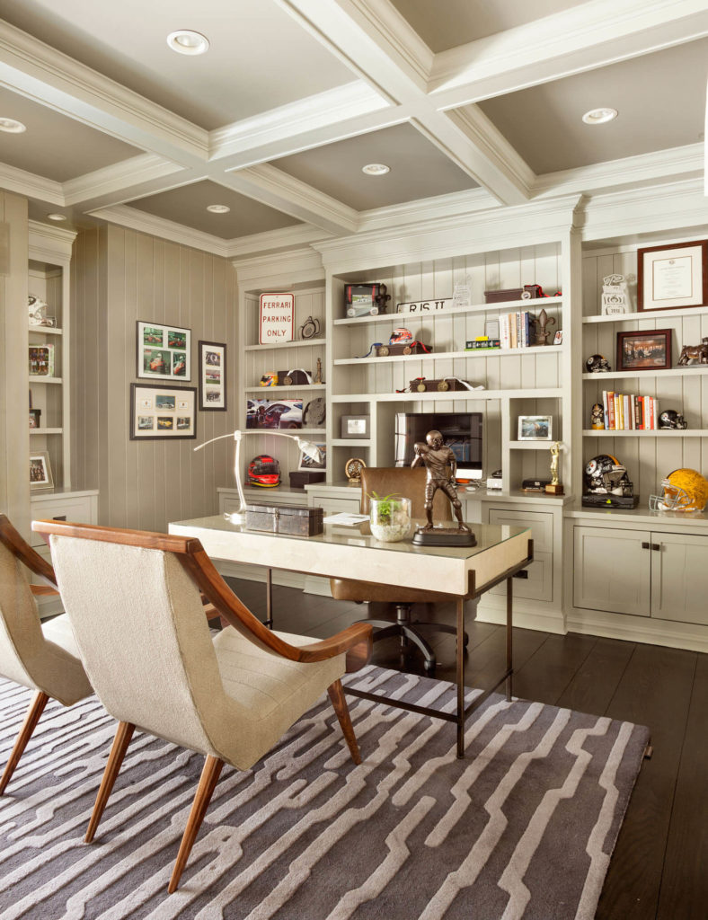 The formal study has a very traditional, elegant design and built-in shelving behind the spacious desk.
