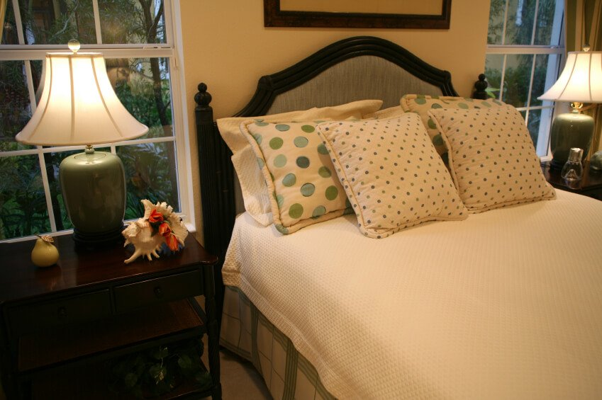 This cheerful bedroom adds a touch of whimsy with green and baby blue polka dotted pillows. The cream linens of the blanketing offer a beautiful canvas that allow these accents to stand out. Larger polka dotted pillows are placed behind more delicately dotted square accent pillows, both of which tie the room together and coordinate with similar color splashes throughout the room.