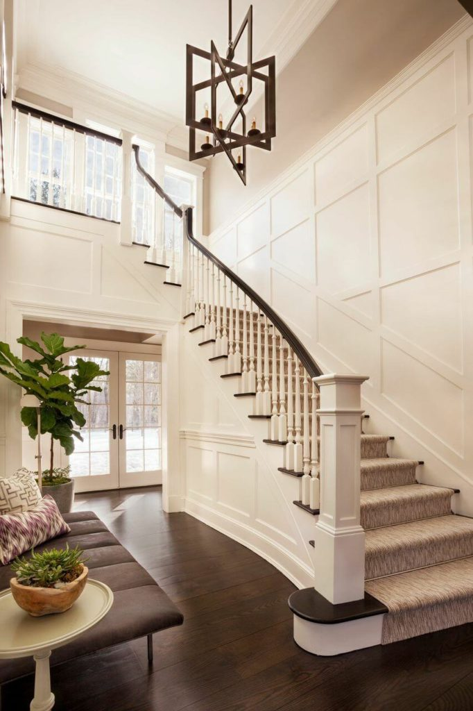 The entrance to the family home has beautiful wide plank wood floors and a gently curving staircase with light carpet treads. Wainscoting along the walls adds a subtle sense of sophistication. A small settee near the entrance is perfect for removing shoes. French doors lead directly to the back courtyard.