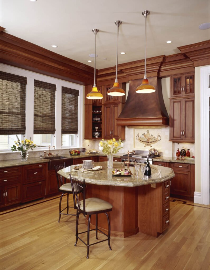 The light floor used in this kitchen brings out the light shades of the countertop and backsplash and allows for the reddish color of the cabinetry to stand out.