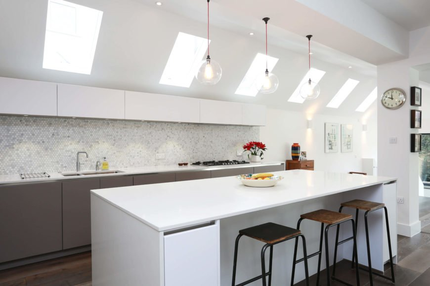 The kitchen features an intricate micro-tile backsplash over sleek white countertops, plus a trio of bare glass pendant lights above the island.