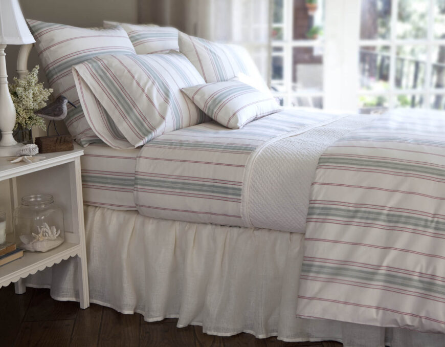 Throw pillows in various sizes coordinate perfectly with the striped bed linens. The rectangular accent pillow allows a bit of variation in the horizontal stripes of its fabric against the vertical stripes of the linens.