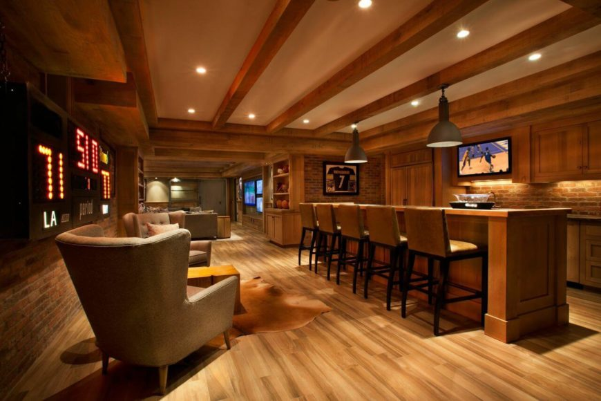 In the basement of the home is the family room, a two sectioned space that includes a lengthy bar that is facing a wall-mounted television. The back wall is decorated with a scoreboard.