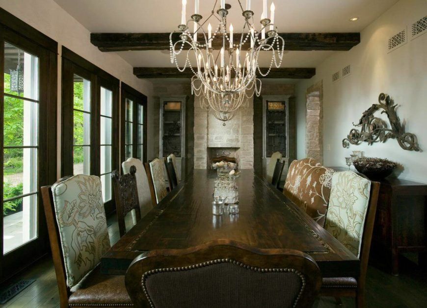 Connected to both the kitchen and living room is the formal dining room, which also contains a stone fireplace and a beautiful ornate dining table. Windows line the left wall of this room, letting in natural light to supplement the three matching chandeliers above the table.