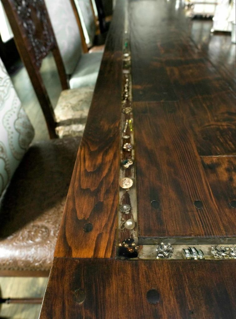 A ridge in the table is filled with antique rings, brooches, and earrings and covered in glass. These details add a bit of shine to the solid table.