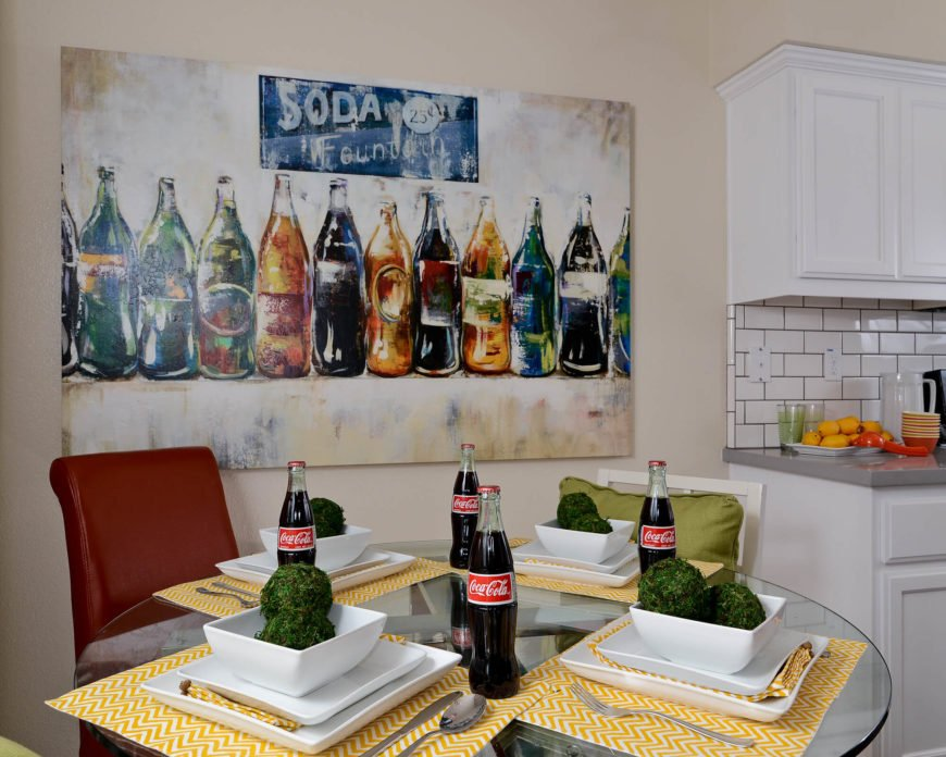The glass topped round table is decorated with white dishes and Cola bottles that mirror the pop art on the wall above.