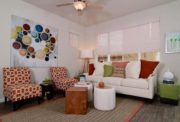 In the living room, the trio of smaller tables replaces a traditional coffee table in appealing fashion, while the eclectic burst of colors makes for visually arresting surroundings.