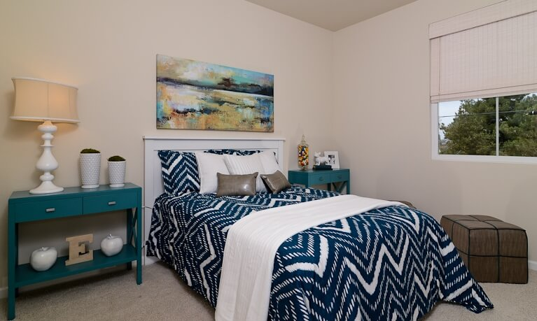 The primary bedroom features a striking mixture of blues and white, with a pair of bold side tables flanking the bed. A large oil painting hangs above, while cubic ottoman sits below the window.