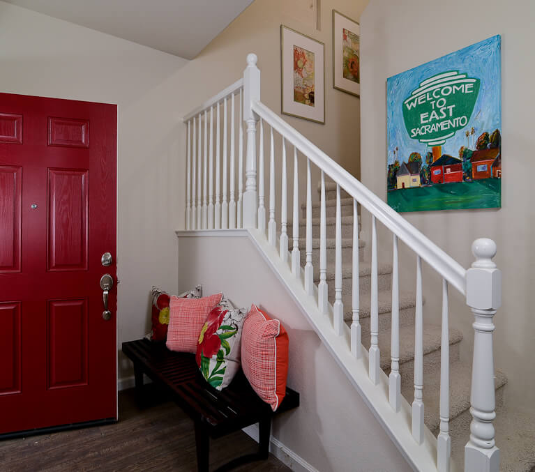 The foyer sports white painted staircase and rich dark wood bench, spiked with bold colors, from the red front door to the pillows and paintings spread throughout.