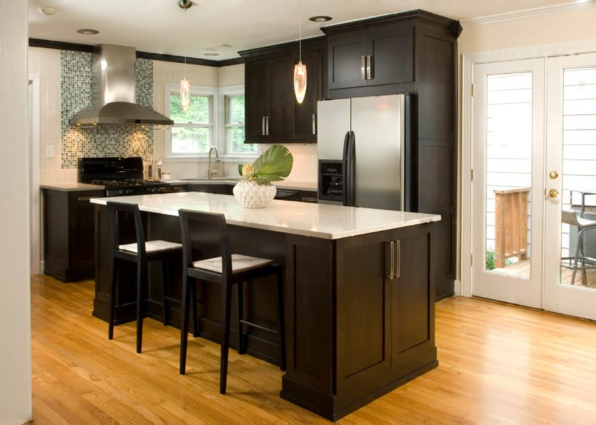 The bright, simple kitchen is weighted by the use of dark cabinets. The tile backsplash behind the stove hood adds a beautiful focal point.