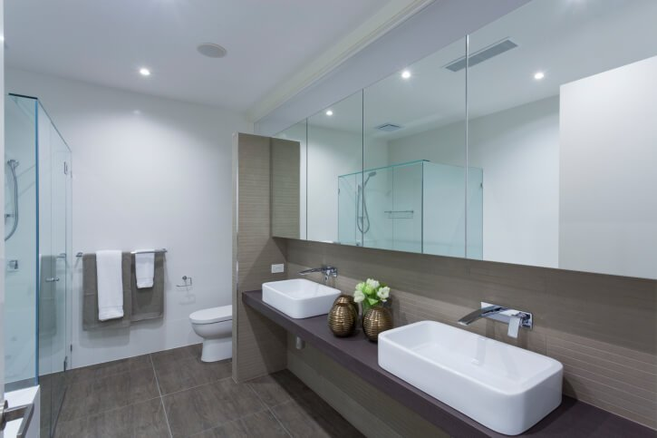 This modern minimalist bathroom design sports a floating vanity with rectangular vessel sinks and wall-mounted faucets. Dark brown floor tiling adds contrast with white walls and glass shower enclosure.