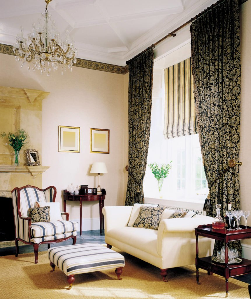 These beautiful curtains are pattern heavy, in black and beige. They form a striking contrast to the striped chair and solid loveseat.