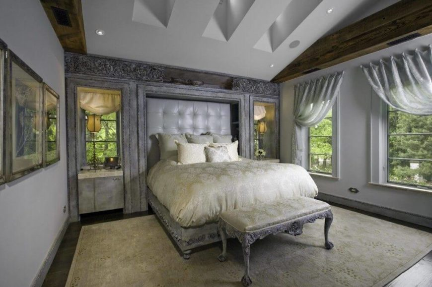 A white and gray bedroom with an inset button-tufted headboard in faux leather. The bed frame is ornately carved and matches the bench at the foot and the molding above the built-ins.