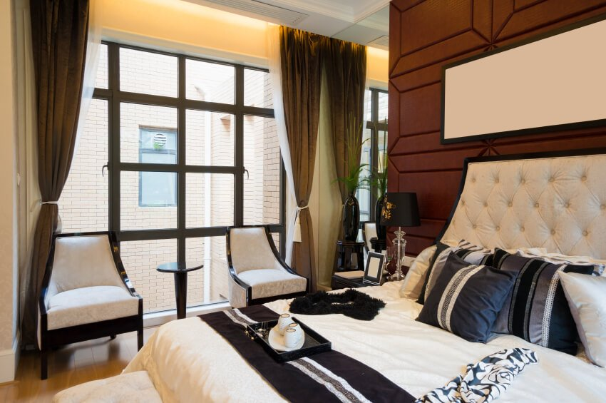 This outstanding bedroom features a luxurious ivory padded headboard against a chocolate backdrop. Black, white, and shimmering gray throw pillows mimic the colors seen in the stunning accent chairs, as well as the black trim of the windows overlooking an ivory brick wall outside.