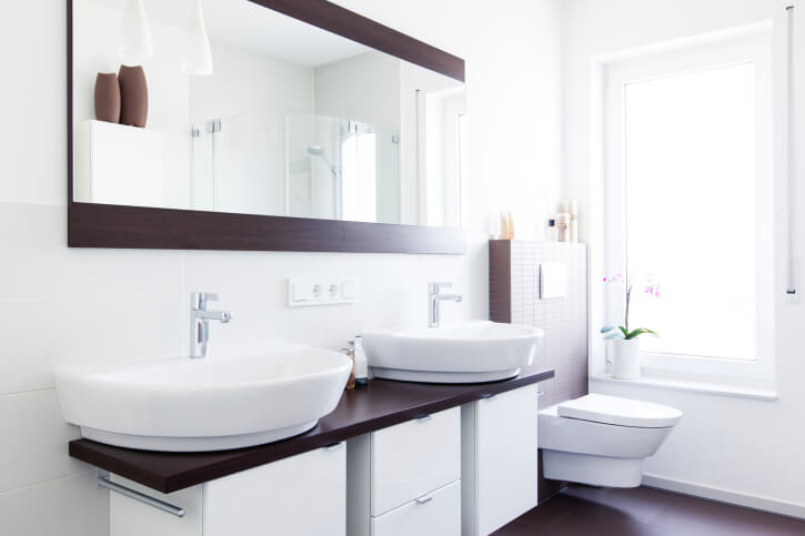 This bright bathroom features a high contrast look with dark hardwood flooring, countertop, and mirror frame in a largely white space. A pair of large vessel sinks stands below the large format mirror.