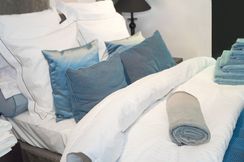 his pillow arrangement features beautiful blue pillows against delicately trimmed and subtly striped accent pillows matching the linens. A rolled accent pillow can be seen propping up the arrangement, while the sheen of peacock-blue catches the eye.