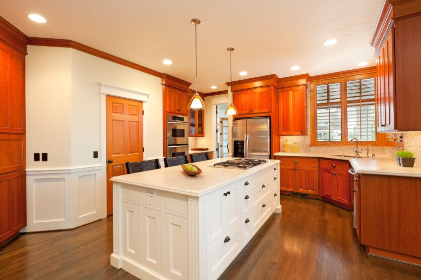 This bold kitchen features a lot of red hues in the wooden cabinets, but a more natural note in the wooden flooring. The fierce color contrast keeps this room bright and beautiful.