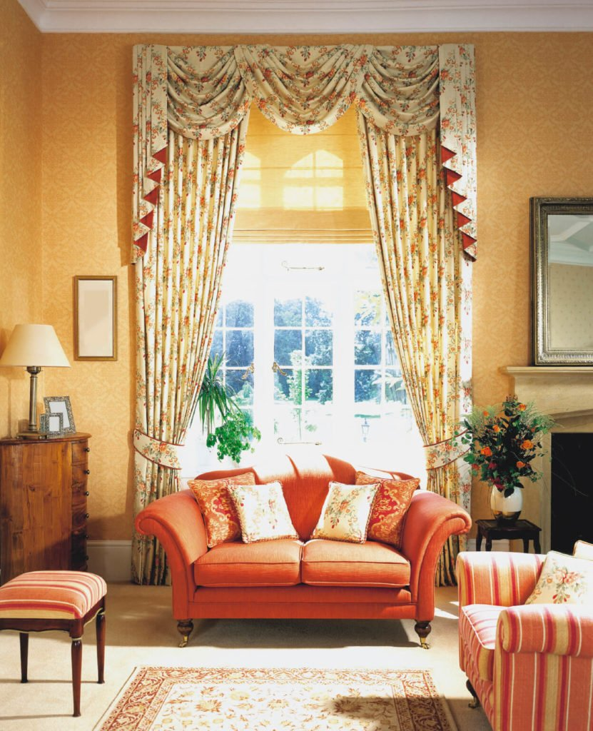 This traditional living room has a few pops of color in the furniture upholstery, which pull from the floral pattern of the drapes.